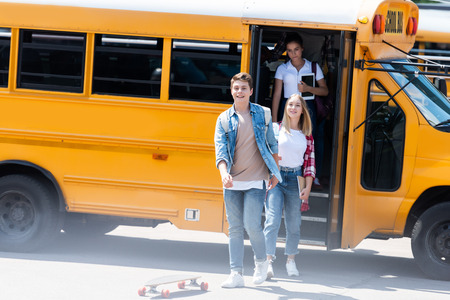 group of teen students walking out of school bus after school