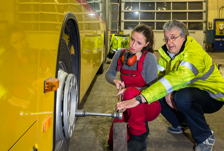 24534770 - yong woman, trainee with the master, change wheel of a buses in the work hall